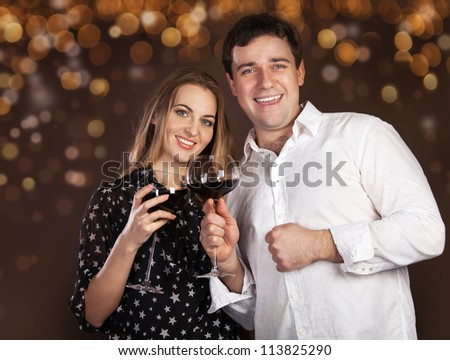 Portrait of a happy young couple with red wine on blurred lights background - stock photo