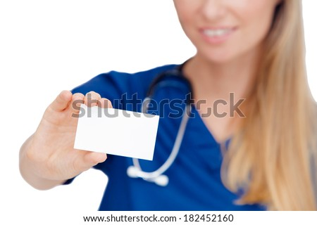 Portrait of a happy young Doctor holding a blank sheet of paper on white to write your text. Isolated on white background. - stock photo