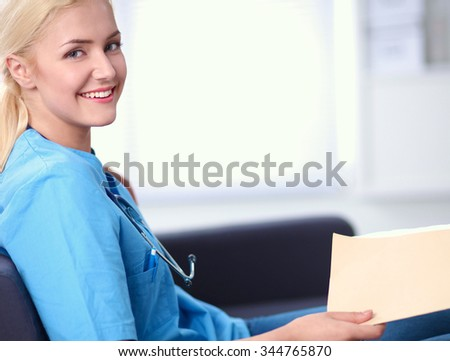 Portrait of a happy young doctor sitting on the sofa with folder - stock photo