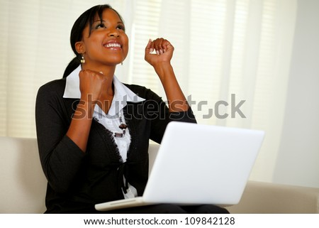 Portrait of a happy young entrepreneur woman celebrating a business victory on laptop and looking up while sitting on couch - stock photo