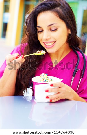 Portrait of a happy young female doctor eating frozen yogurt, Vertical shot. - stock photo