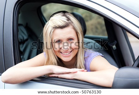 Portrait of a happy young female driver - stock photo