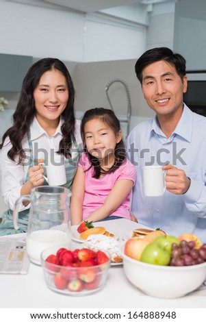 Portrait of a happy young girl enjoying breakfast with parents at table in the kitchen
