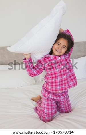 Portrait of a happy young girl holding up a pillow in bed at home - stock photo