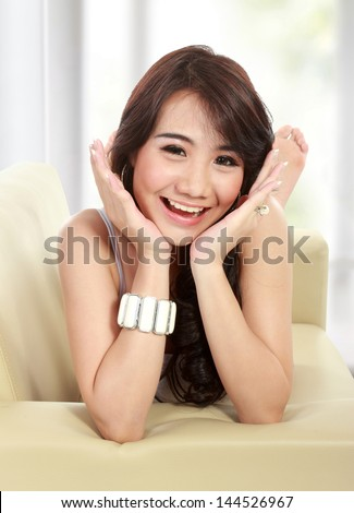 Portrait of a happy young girl lying on sofa and looking at camera