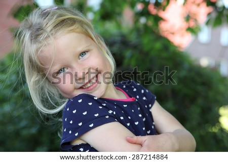 Portrait of a happy young girl outdoors in garden - stock photo