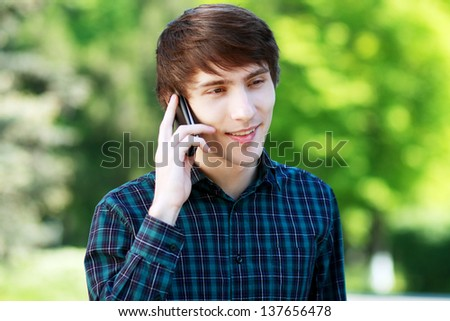 Portrait of a happy young guy talking on mobile phone in a park - Outdoor - stock photo
