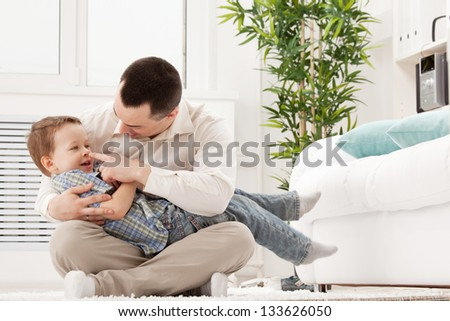Portrait of a happy young guy with son - stock photo