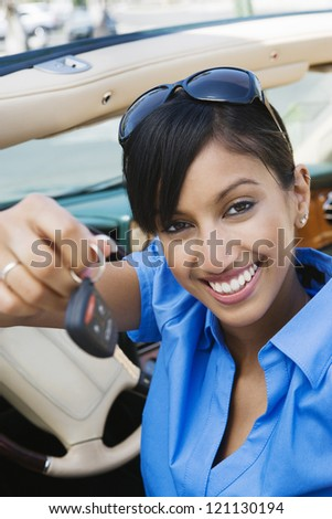 Portrait of a happy young Indian business woman showing new car keys