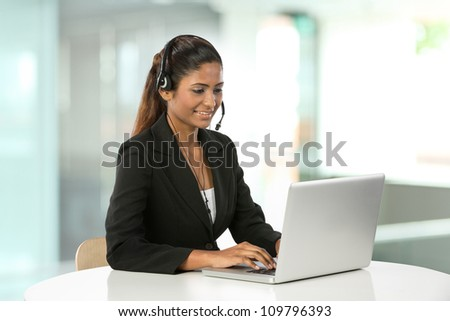 Portrait of a happy young Indian female call centre employee with a headset.