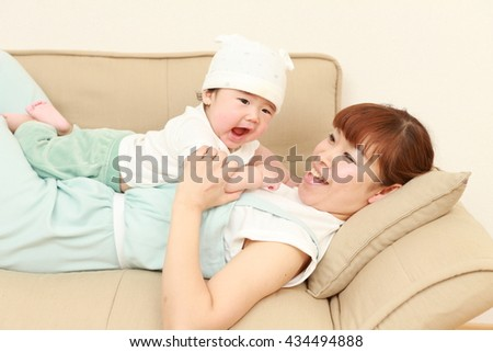 portrait of a happy young Japanese mom and her baby - stock photo