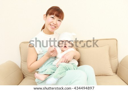 portrait of a happy young Japanese mom and her baby