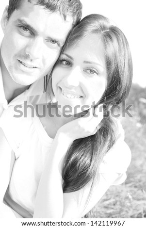 Portrait of a happy young latin hispanic couple sitting on grass in a park - Outdoor