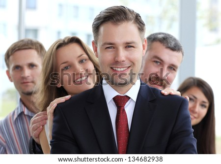 Portrait of a happy young male business leader standing in front of his team