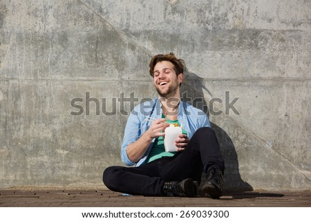 Portrait of a happy young man eating chinese takeaway food with chopsticks - stock photo