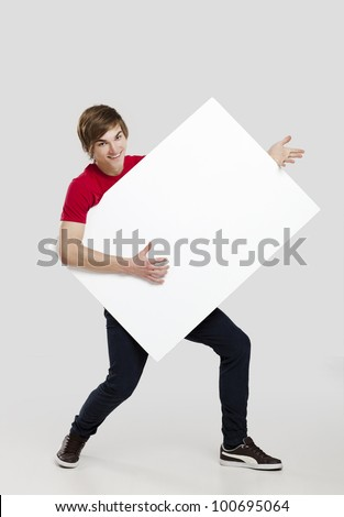 Portrait of a happy young man holding and playing with a blank white card - stock photo