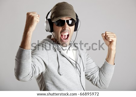 Portrait of a happy young man listen music with headphones - stock photo