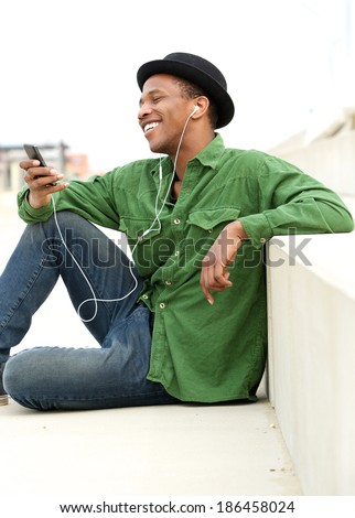 Portrait of a happy young man listening to call on mobile phone with earphones - stock photo