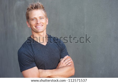 Portrait of a happy young man looking at camera, standing outside