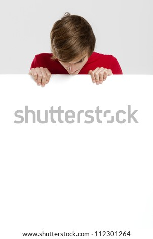 Portrait of a happy young man looking to a blank white card - stock photo