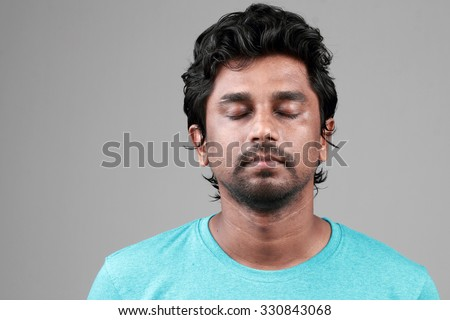 Portrait of a happy young man of Indian origin with eyes closed - stock photo