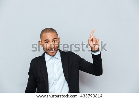 Portrait of a happy young man pointing finger up at something interesting isolated on gray background - stock photo