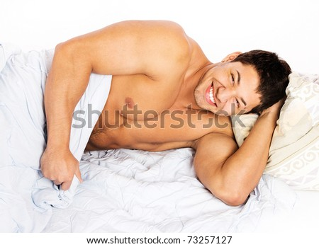 Portrait of a happy young man relaxing on bed at home