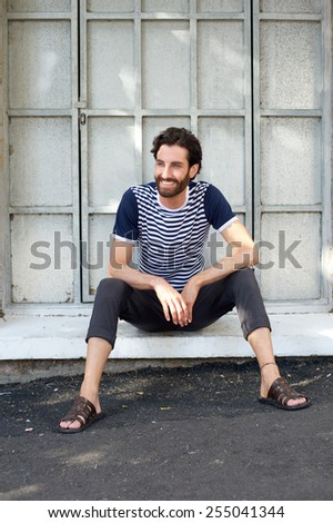 Portrait of a happy young man sitting in frame of a window - stock photo