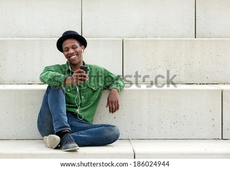 Portrait of a happy young man sitting outdoors with mobile phone - stock photo