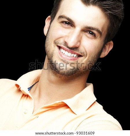 portrait of a happy young man smiling against a black background - stock photo