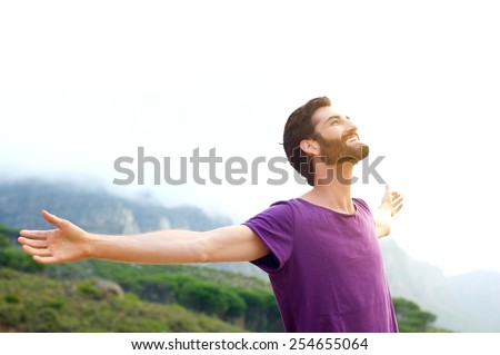 Portrait of a happy young man standing in nature with arms spread open - stock photo