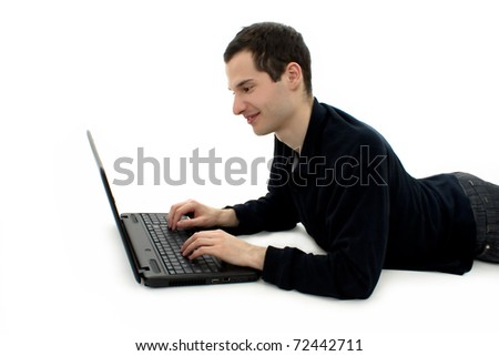 Portrait of a happy young man surfing on laptop, lying down. Isolated on white background.