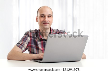 Portrait of a happy young man using a laptop. Indoor - stock photo