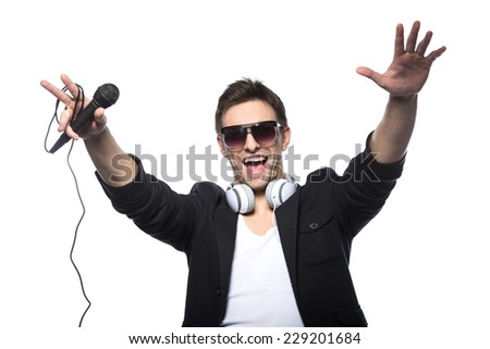 Portrait of a happy young man with a microphone and headphones on a white background. - stock photo
