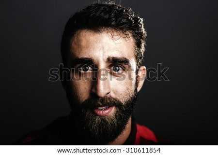 Portrait of a happy young man with beard smiling against gray background - stock photo