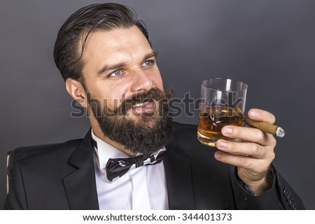 Portrait of a happy young man with retro look sitting in an armchair,smoking and holding a glass of whiskey over gray background