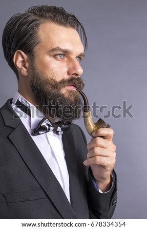 Portrait of a happy young man with retro look smoking pipe