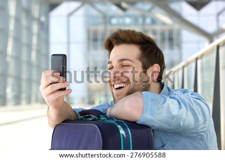 Portrait of a happy young man with traveling bag looking at cell phone - stock photo