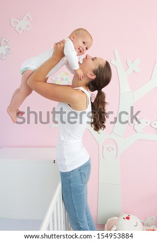 Portrait of a happy young mother lifting cute baby out of crib in bedroom - stock photo