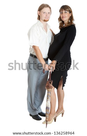 Portrait of a happy young pregnant woman and her husband with umbrella - stock photo