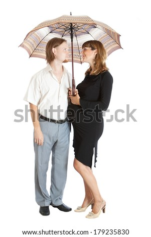 Portrait of a happy young pregnant woman with her husband under umbrella - stock photo