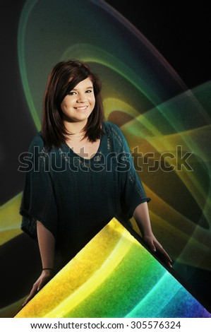 Portrait of a happy young teen leaning over a bright triangle and before swirls on black.   - stock photo
