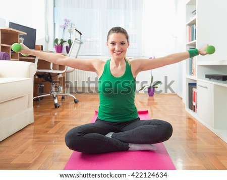 Portrait of a happy young woman exercising at home. She is sitting crossed-legged on the exercise mat and doing exercise for her arms with a pair of green hand weights.