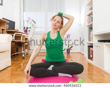 Portrait of a happy young woman exercising yoga at home. She is sitting crossed-legged on the exercise mat.