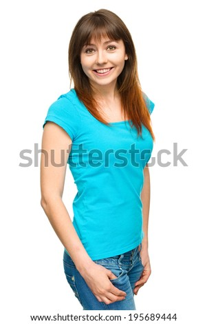 Portrait of a happy young woman holding her hands in pockets, isolated over white