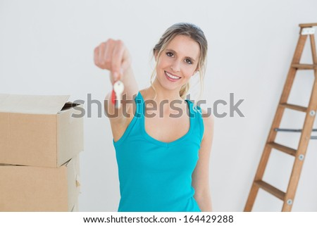 Portrait of a happy young woman holding out with key besides boxes in a new house - stock photo