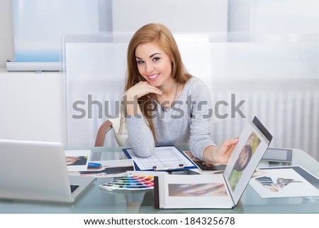 Portrait Of A Happy Young Woman Holding Photo Album - stock photo