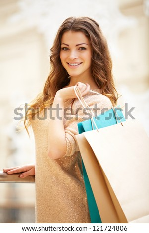 Portrait of a happy young woman holding shopping bags at the mall