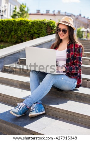 Portrait of a happy young woman in sunglasses sitting on the city stairs and using laptop computer outdoors - stock photo