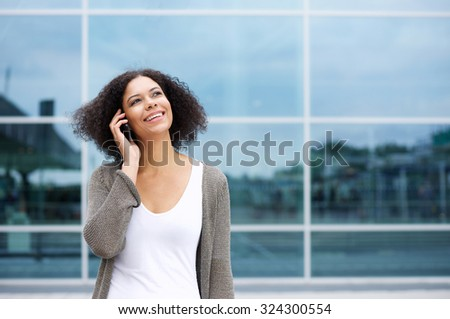 Portrait of a happy young woman listening to mobile phone outside